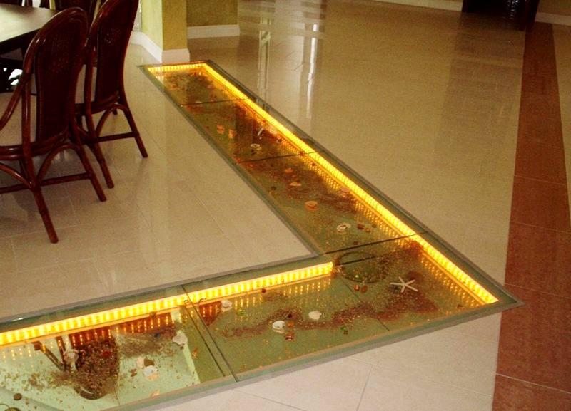 Бывают варианты использования на полу стеклянной плитки с подсветкой