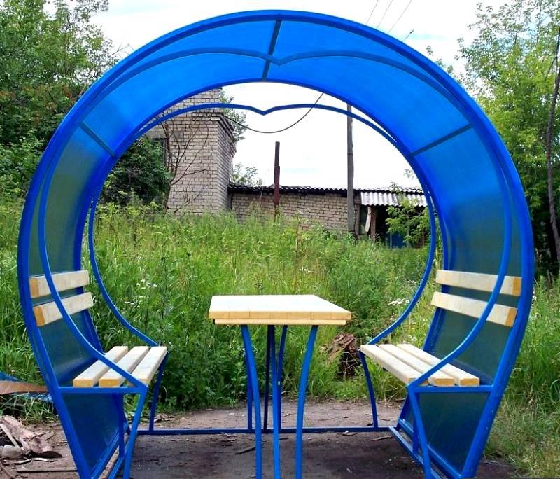 Ещё одна гениальная в своей простоте идея создания металлической беседки. Для её реализации пригодится всего две трубы, согнутые дугой и кусок поликарбоната. Её единственный минус – в такой беседке мангал не поставишь. Его придётся установить рядом, а под навесом разместить стол и садовые кресла