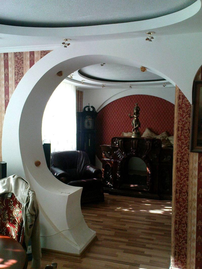 Фигурные потолки из гипсокартона на фотографии дополняют изогнутые арки. Возможность работы со сложными по форме поверхностями – еще одно преимущество материала