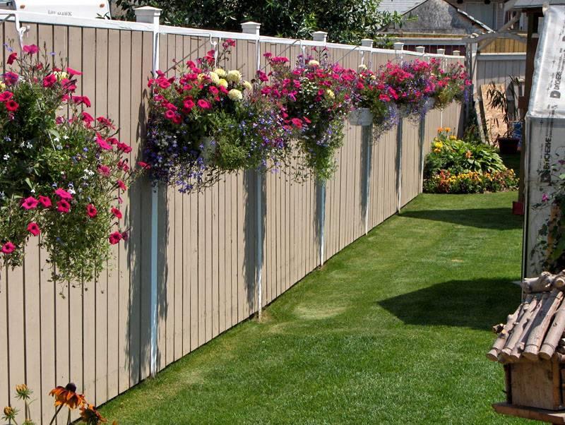 Подвесные горшки с цветами на пластиковом заборе