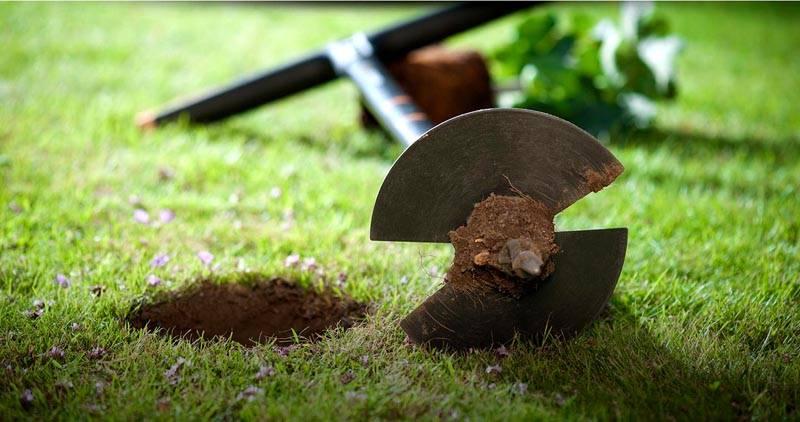 С помощью садового бура высверливаются отверстия для установки и бетонирования столов