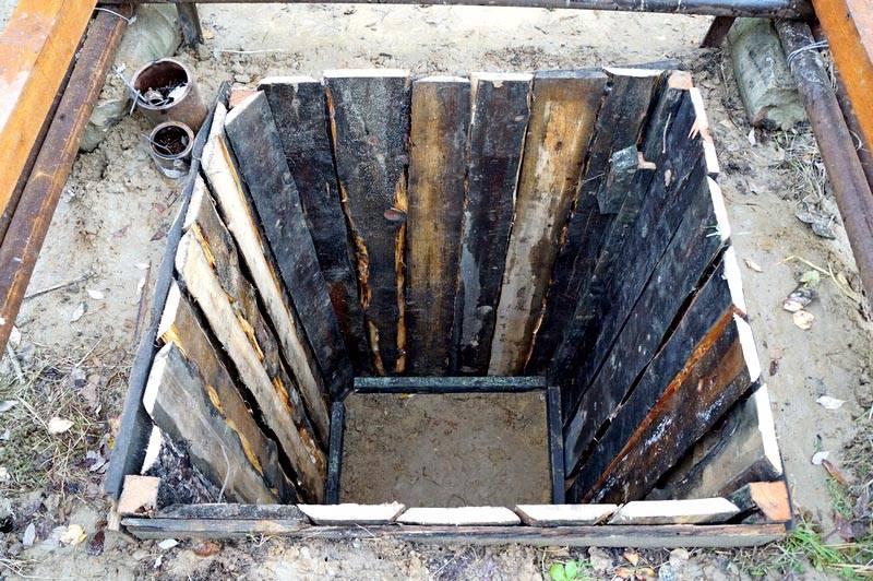 Яма под туалет, укрепленная деревянными досками