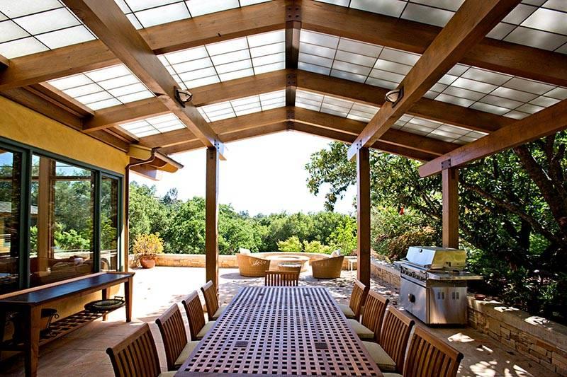 Часть пристройки террасы к деревянному дому можно защитить от непогоды навесом, другую – оставить открытой