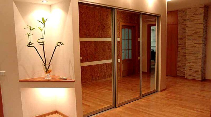 Шкаф-купе с зеркальными дверями расположенный в нише холла визуально увеличивает пространство