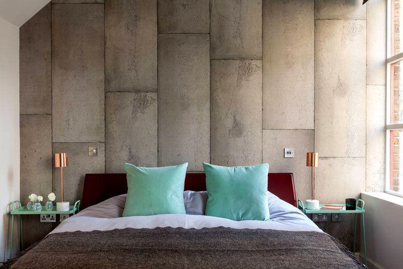 Акцентная стена в спальне у изголовья кровати выполнена из цементных панелей