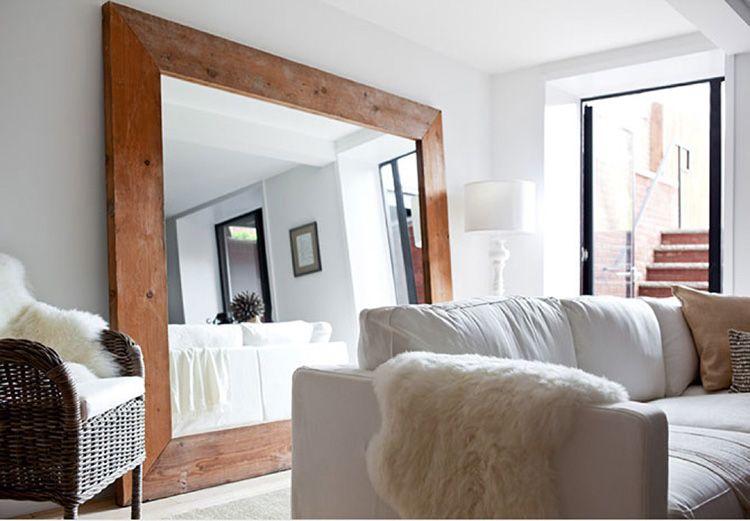 Большое зеркало в деревянной раме добавит ещё больше света в помещении