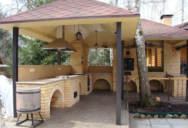 Летняя кухня с кирпичными и металлическими столбами и мягкой кровлей