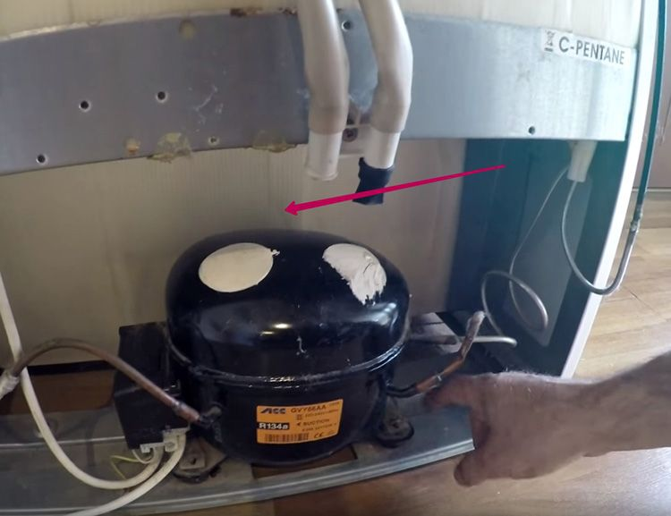 Стрелка указывает место, куда можно установить брусок для плотной фиксации компрессора