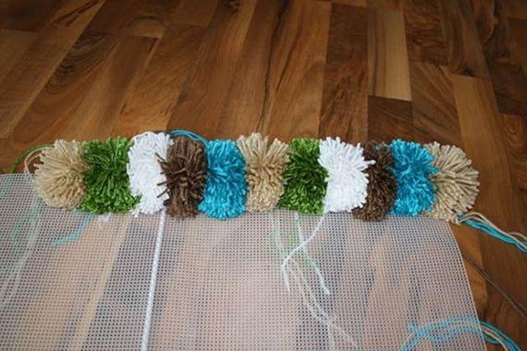 Далее выкладываем получившиеся помпончики на сетку, прикрепляя их на клей или привязывая на нить, которая осталась после стягивания помпона.