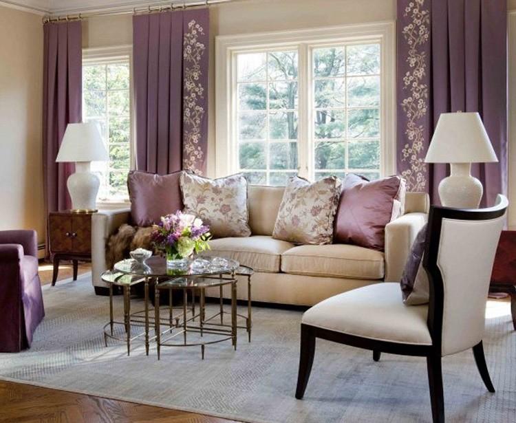Фиолетовый цвет в интерьере бежевой гостиной представлен текстилем