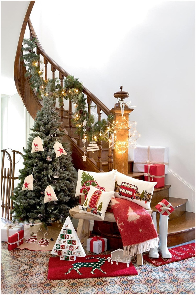 Прихожая, переходящая в лестницу, будет смотреться особенно торжественно, если разместить там небольшую ёлку с коробками, задекорированными подарочными упаковками.