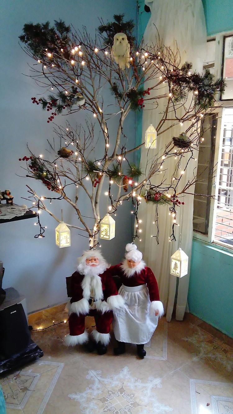 В обход традиций: свободный угол прихожей хорошо дополнится ветками дерева, и отнюдь не хвойного. Пара гномов или Дед Мороз сделают картину до новогодним идеалом.