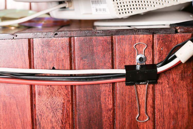 Обычный канцелярский зажим прочно удержит пучок проводов и может крепиться к столу саморезом или болтом