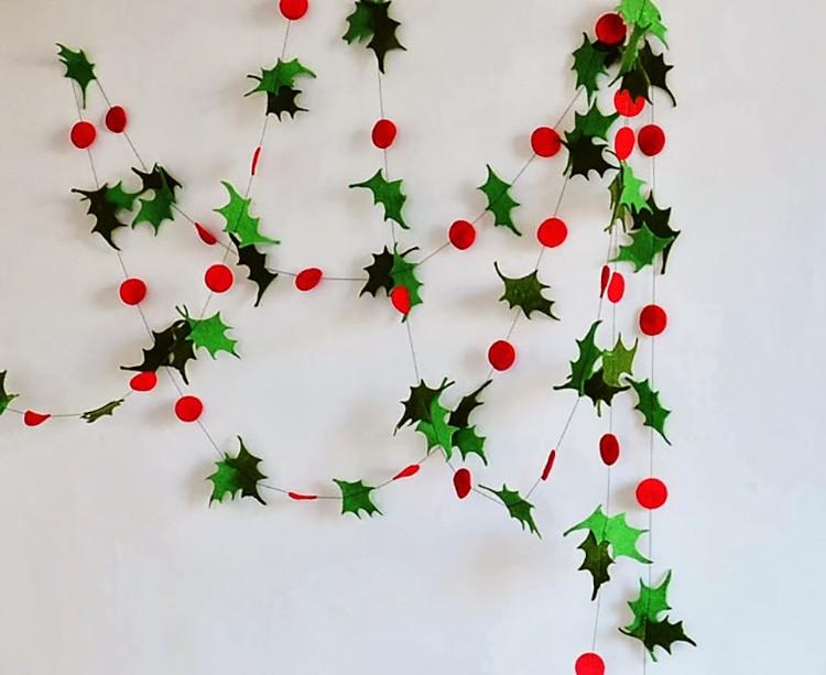 Используем бумагу зелёных оттенков и красных. Из зелёного цвета нам нужно вырезать листья остролиста, из красных — ягоды. Между собой все элементы соединяются с помощью клея и нитки.