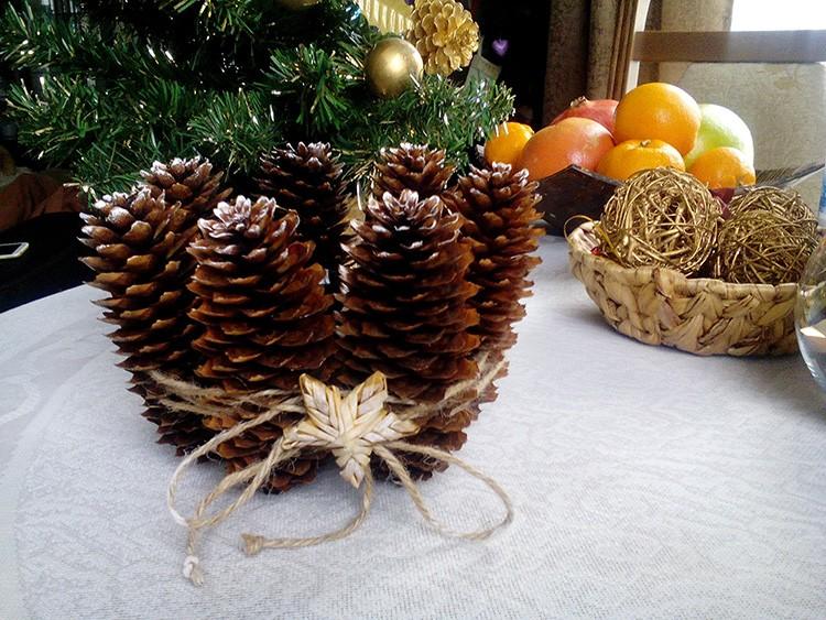 На картонную основу наклеивают несколько еловых шишек и связывают их лентой. По центру будет стоять свеча.