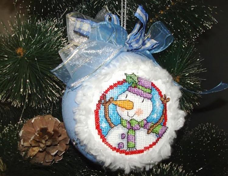 Иногда вышивку на шаре располагают с помощью горячего клея и декора.