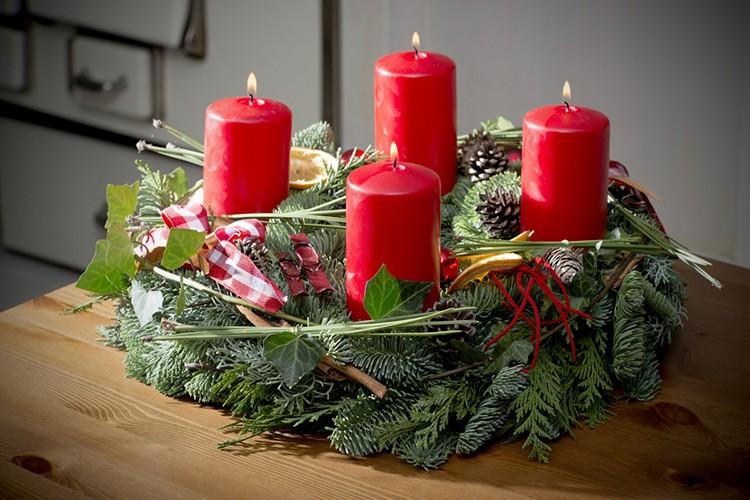 Еловый венок послужит ложем для свечей, если вставить между веток рюмки под основание свечек.
