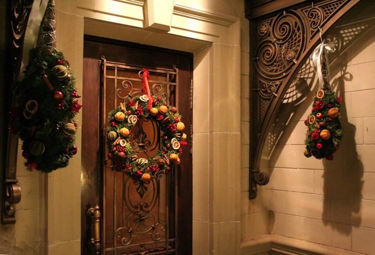Новогодний венок можно закрепить на декоративных элементах двери