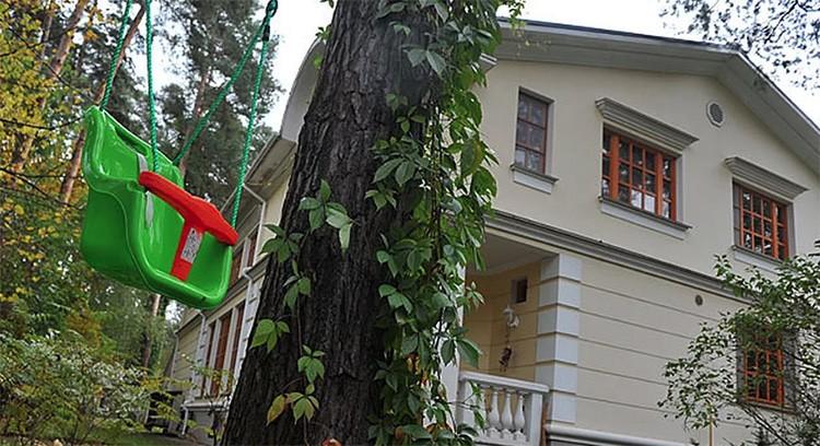 Фасад дома окрашен в светлой тёплой гамме, а окна – в коричневой. Такое сочетание прекрасно гармонирует с природой