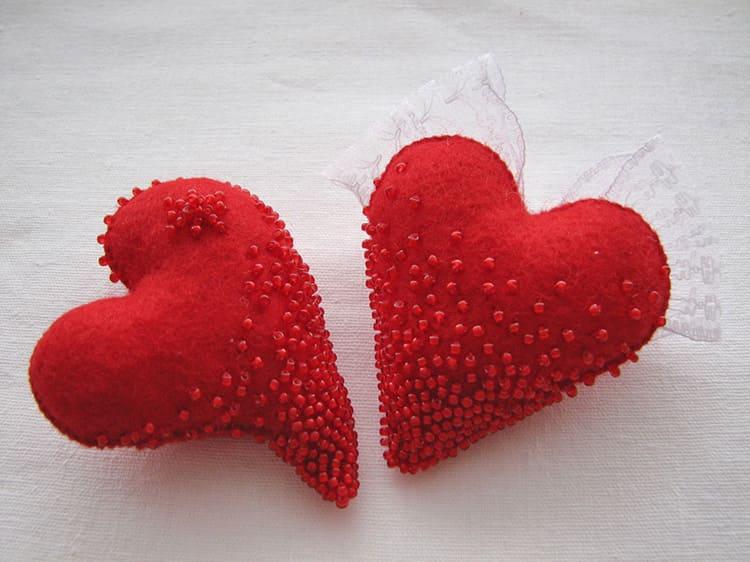 Из материала яркого красного цвета вырезают два одинаковых сердца, декорируют каждую деталь бисером, затем сшивают их, не забыв набить синтепоном.