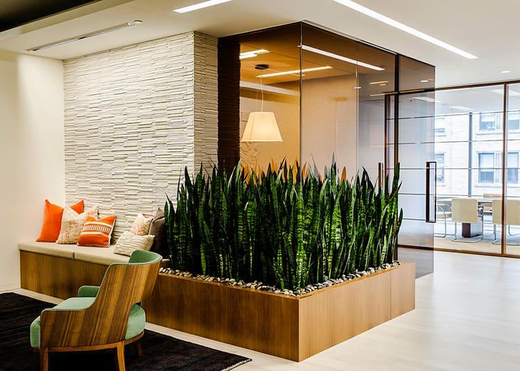 Большое кашпо-грядка с яркими растениями смотрится как мебель