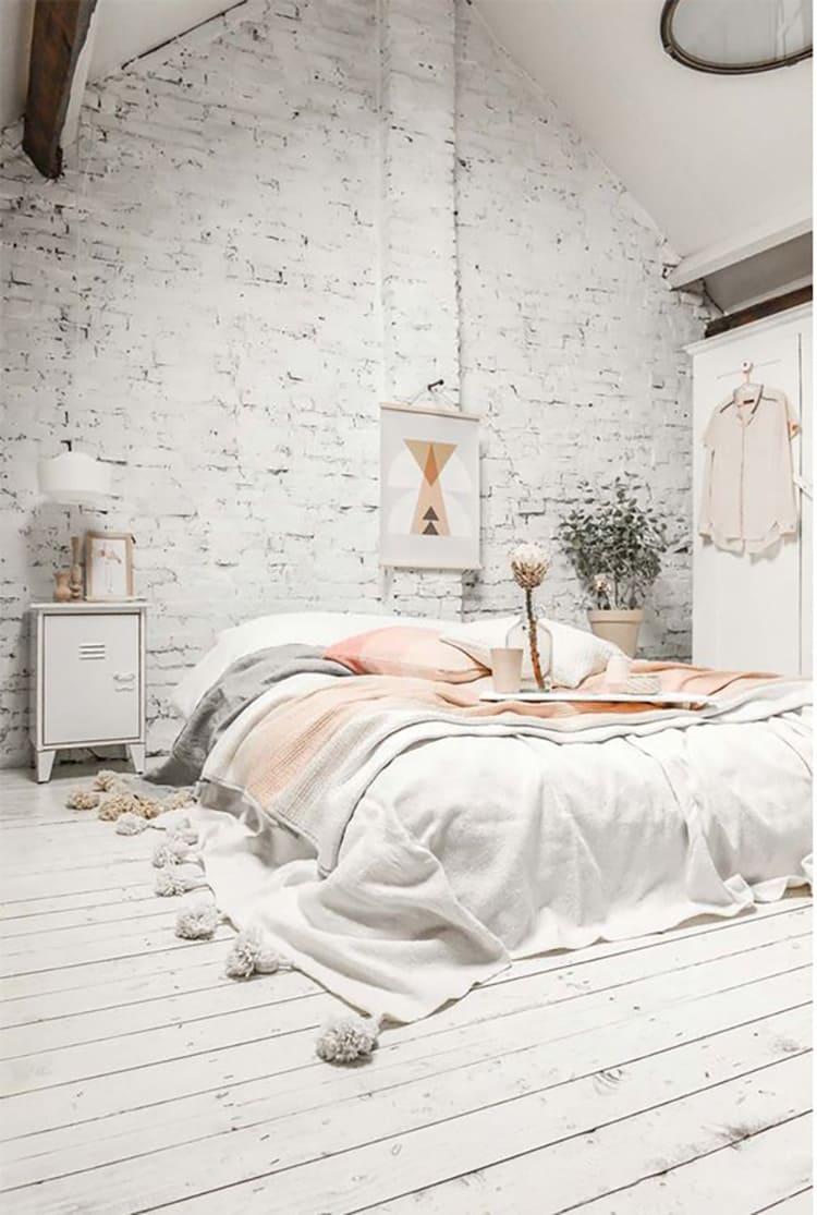 Деревянный пол и окрашенный кирпич вполне гармонично сочетаются в спальне