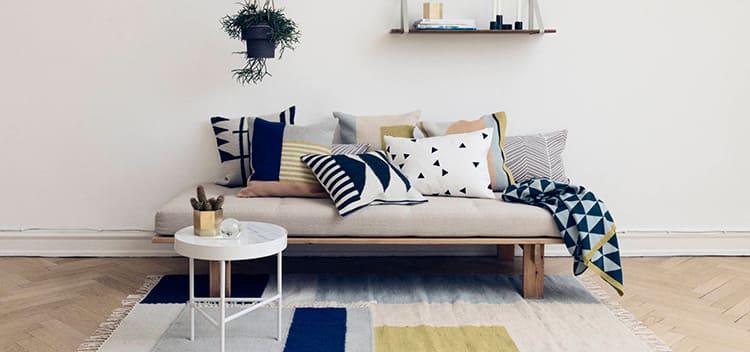 Предметы мягкой мебели из натурального дерева уместно украсить тёплыми пледами и подушками с фольклорными узорами