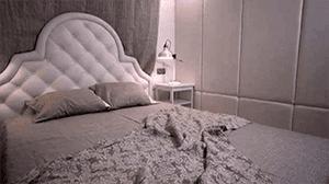 Изголовье кровати оформлено в одной гамме со стеновыми панелями.