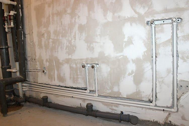 Сложнее размещать трубы в толще стены. В этом случае придётся штробить канал, утеплять его минеральной ватой, укладывать трубы и заново выравнивать поверхность