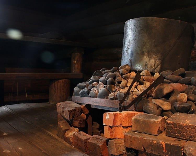 Не старайтесь выложить камни очень плотно, между ними должно оставаться пространство для выхода дыма. Сверху на камни ставят металлический бак для горячей воды