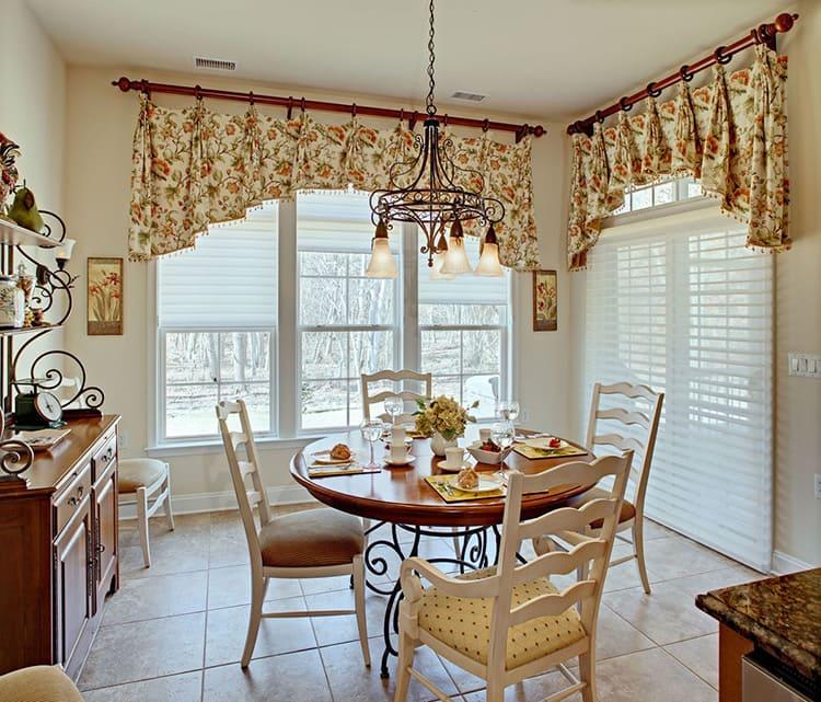 Для декорирования окон на кухне обычно используют короткие занавески, дающие больший приток естественного света