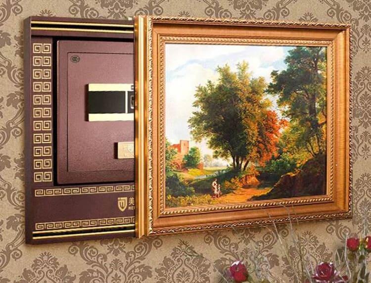Скрыть такое хранилище можно под картиной, за спинкой дивана или декоративным панно. Установка такого устройства дело довольно хлопотное