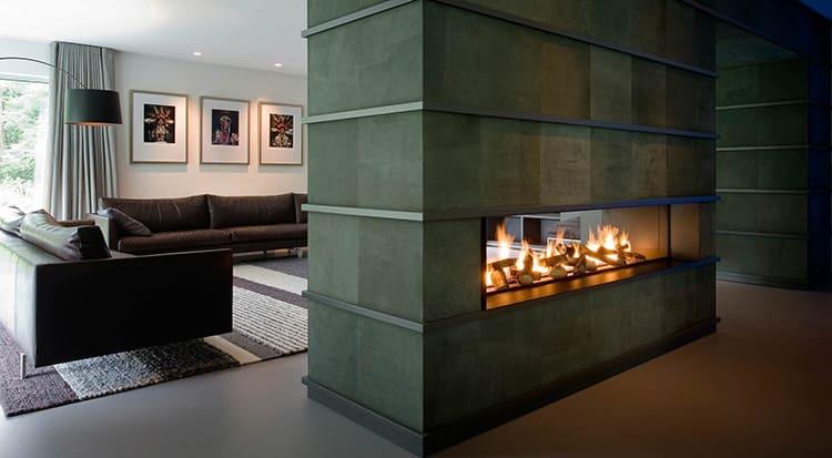 Большой камин в торцевой части комнаты или в перегородке поможет визуально расширить площадь и сделать помещение просторнее