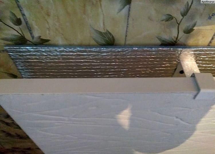 Чтобы тепло направлялось в помещение, а не обогревало стену, на место крепления сначала приклеивают утеплитель фольгой наружу. Она будет отражать тепло