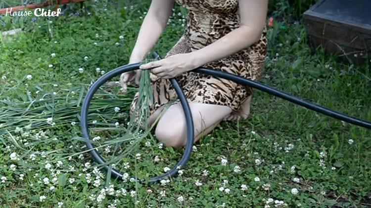 Кольцо из шланга я обмотала травой, закрепляя зелёный материал ниткой и постепенно добавляя пучки