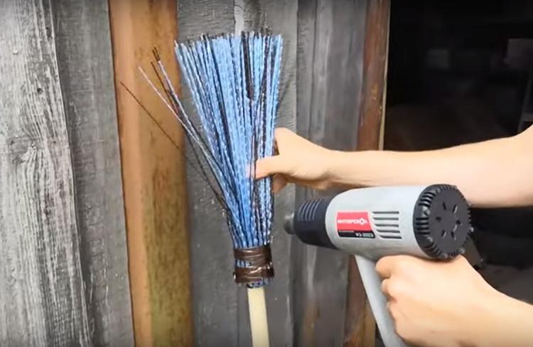 Для этой цели снова используем строительный фен. Нужно направить поток горячего воздуха в основание метлы у самой стяжки и вручную слегка разогнуть прутья в стороны