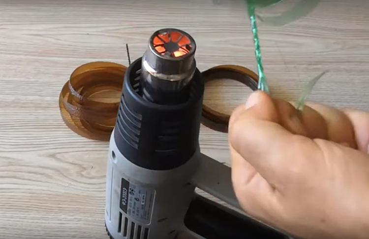 Включите фен и сначала пальцами сверните кончик полосы в несколько витков