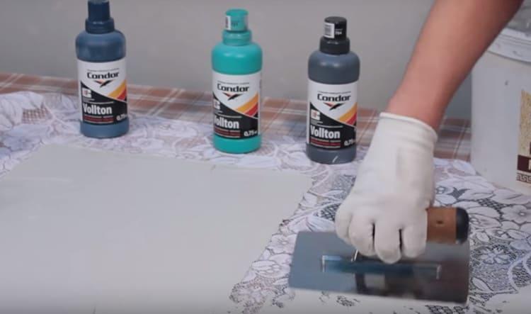 С помощью шпателя прямо поверх ткани нанесите фактурную краску или штукатурку. Проглаживайте, чтобы краска проникала сквозь сеточку рисунка. Делать это придётся довольно быстро, потому что дальнейшие манипуляции с тканью должны производиться, пока краска-штукатурка не высохла