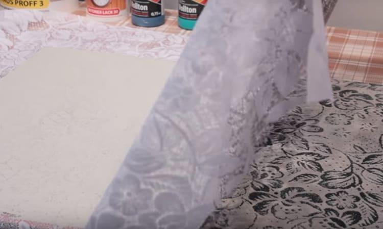 Как только вся поверхность заполнится, нужно снять ткань движением сверху вниз, отнимая её от стены и стараясь не повредить рисунок