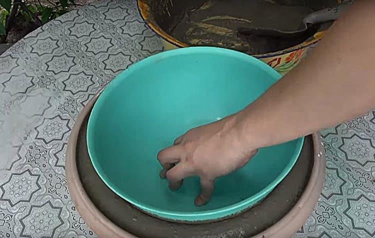 Внутреннюю часть формы необходимо поместить строго по центру и аккуратно погрузить в заливку. Вытесненный за край бетон нужно удалить