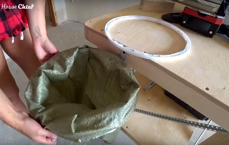 Я отрезала обод от ведра от краски и обрезала крышку. Между ободом и крышкой можно закрепить мешок для мусора. А сам обод зафиксировала подвижным держателем
