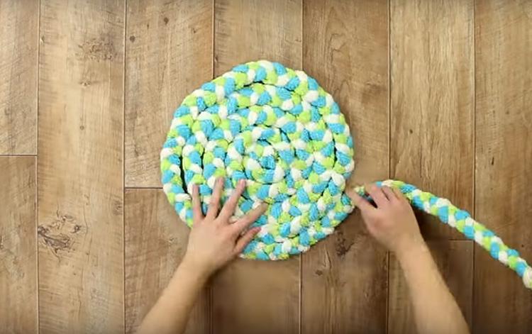 Собирать коврик нужно обязательно на ровной поверхности. Закрутите косу спиралью, стараясь ровно располагать её, чтобы жгут не перекручивался. Если свернёте косу плоской стороной наружу – получится тонкий коврик, если ребром – толстый, но материала потребуется почти вдвое больше