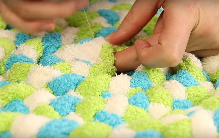 Чтобы собранный коврик держал форму, нужно простегать его ниткой так, чтобы скрепить витки косы между собой. Чем плотнее простегаете, тем прочнее будет ваш половичок