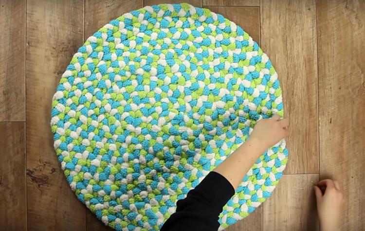 Наружный кончик махровой косы, чтобы он не торчал, нужно заправить под нижнюю часть коврика и прочно пришить к предыдущему витку