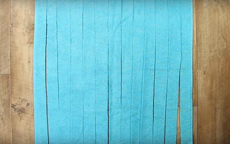 Полотенце я разрезала на полосы по самой длинной стороне. Ширина полос - около 4 см. Если сделать шире – коврик получится потолще и наоборот. Но слишком узкими полосы делать не стоит, они будут рваться
