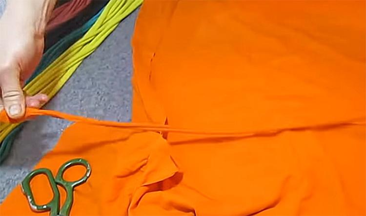 Каждую готовую полоску нужно немного потянуть. Трикотаж не распустится, а деформируется, превращаясь в толстый шнур. Из этих шнуров и будет состоять наш коврик