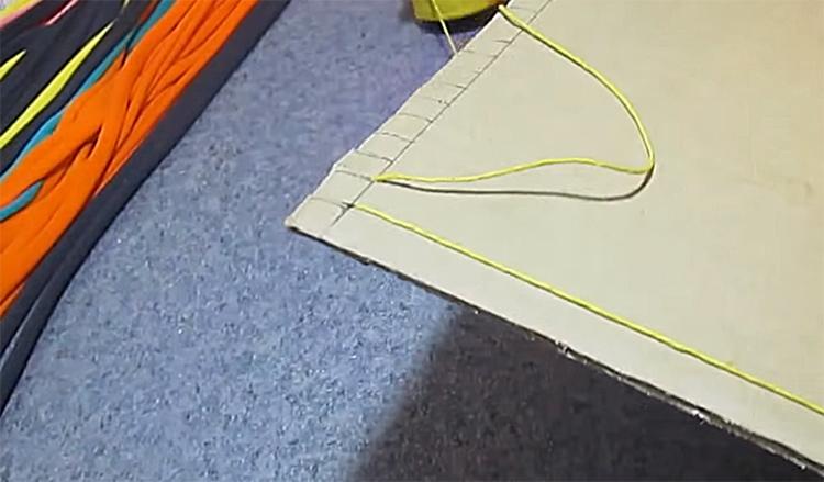 Эту нить, не разрывая, нужно натянуть на картон, огибая зубчики по краям. Натяжение должно быть очень тугим, иначе коврик будет расползаться