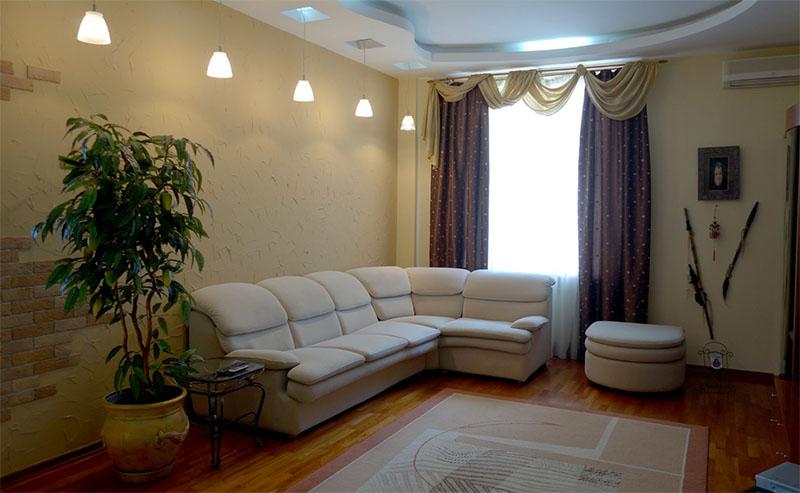 В многоуровневом потолке сделаны небольшие ниши с подсветкой, из которых опускаются подвесные светильники с матовыми абажурами