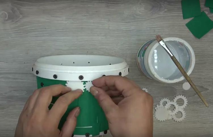 С помощью ПВА наклейте детали шестерёнок, имитируя механизм. Подберите зубчатые колёса так, чтобы они подходили друг к другу