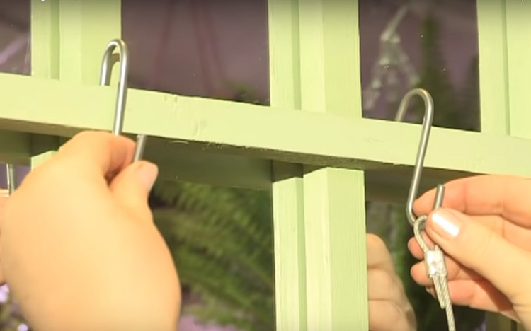 Чтобы было удобно крепить подвесной стеллаж, используйте два металлических крючка. К ним цепляются по две верёвки, на которых держатся бутыли. А сами крючки отлично закрепятся на доске или выступающих гвоздях